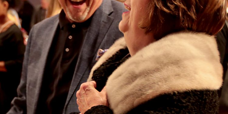 Kathy Qualls shares a laugh with David Ferguson as she decides to purchase the coat she is trying on during RetroFittings 2018, a St. Vincent de Paul fundraising event, at Music Hall in Cincinnati Thursday, Oct. 18, 2018. (CT Photo/E.L. Hubbard)