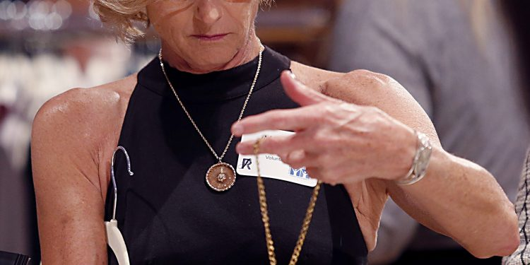 Martha Rhoade examines a necklace during RetroFittings 2018, a St. Vincent de Paul fundraising event, at Music Hall in Cincinnati Thursday, Oct. 18, 2018. (CT Photo/E.L. Hubbard)