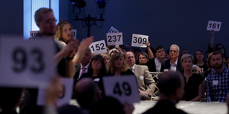 Patrons hold up their numbers to donate during RetroFittings 2018, a St. Vincent de Paul fundraising event, at Music Hall in Cincinnati Thursday, Oct. 18, 2018. (CT Photo/E.L. Hubbard)