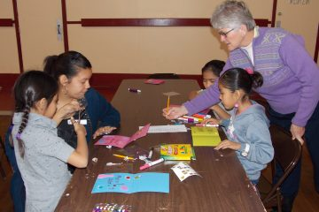 Sister Zoe Brenner helps children make cards for tribal elders. (Courtesy Photo)