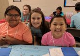 Kylie Schmidt with Savannah Hoover in the background poses with two Navajo children at Summer Bible School. (Courtesy Photo)