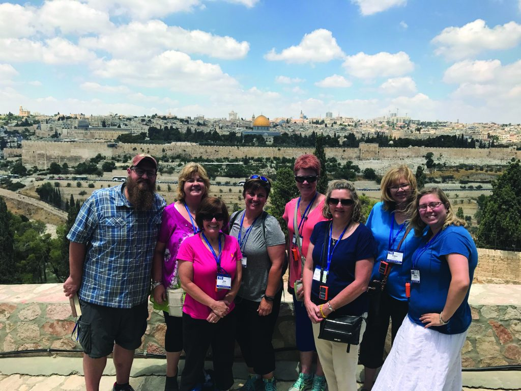 John Leyendecker poses with St. James staff members in 2017 with Jerusalem in the background. Pictured from left are Leyendecker, Melissa Spainhower, Jen Meiners, Karen Wiesman, Sherry Kembre, Carol Feldman, Clare Fox and Emily Ramsey. (Courtesy Photo)