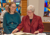 Sister Carol Lichtenberg, Provincial, and Sister Sarah Cieplinski sign the official register of Perpetual Vows, indicating Sarah's gift of her complete life to God. (Courtesy Photo)