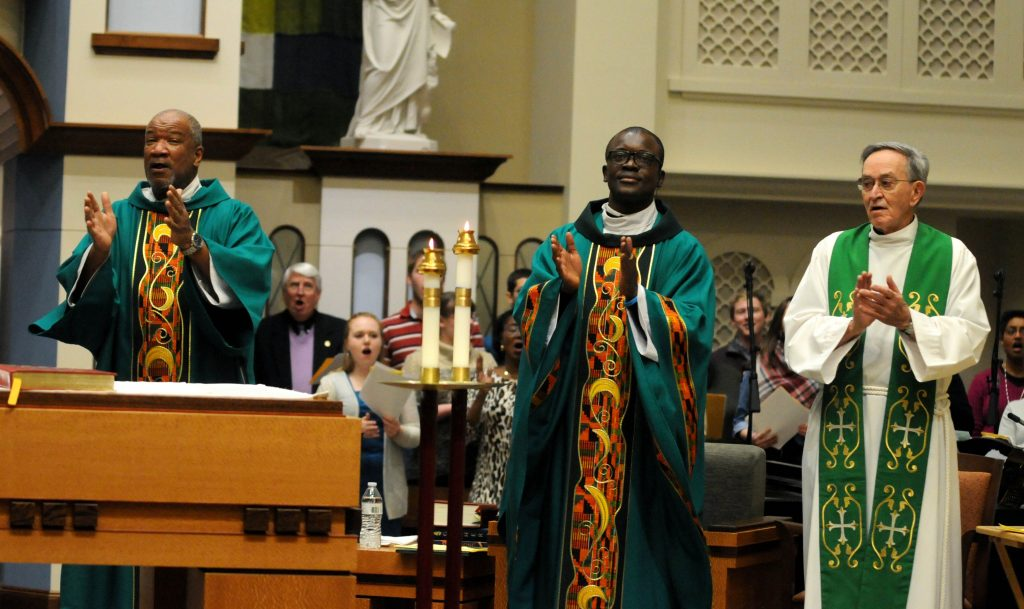 """Rev. Mr. Royce Winters(cq), Father Asibou Kuci(cq) and Father Ted Cassidy(cq) clap along with the congregation during the """"Gathering Hymn"""" of the University of Dayton's """"Mass in Celebration of Black History Month"""" in the Chapel of the Immaculate Conception on Sunday, Feb. 10. (CT Photo/David Moodie)"""