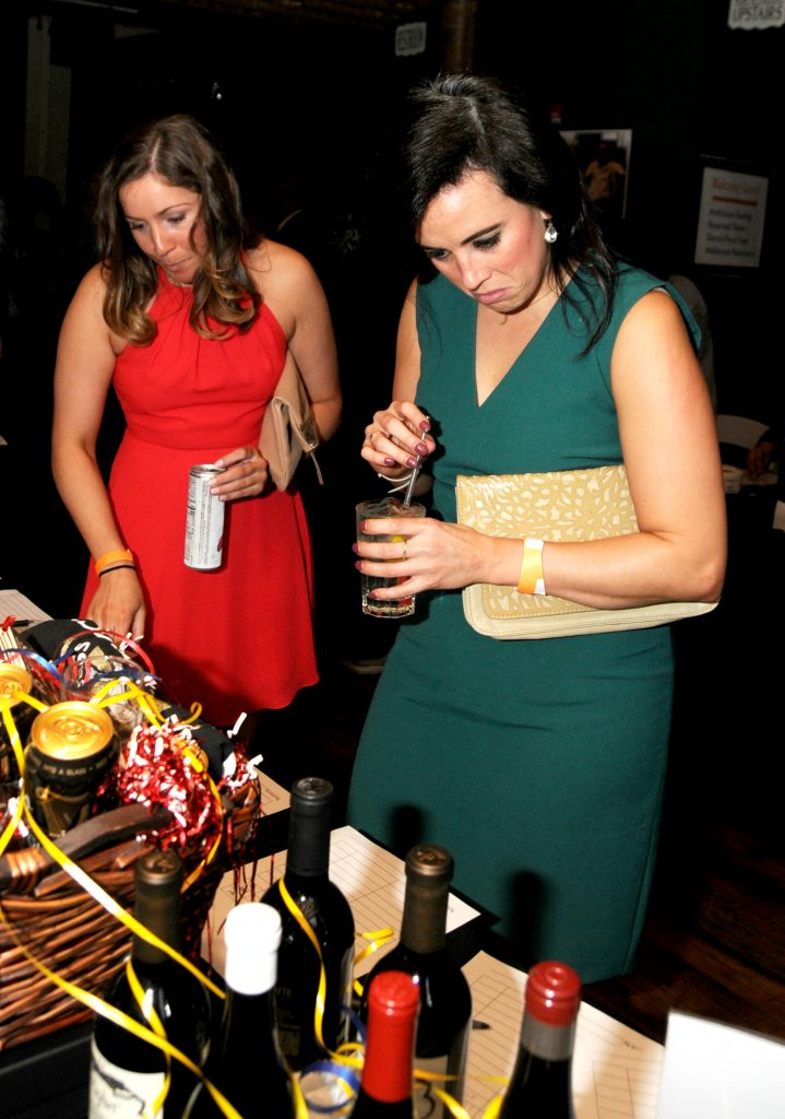 Chloe Hough(cq) and Megan Heimbuch(cq) browse through the silent auction items duriing Catholic Inner Schools Education's Ninth Annual Fundraiser at the Woodward Theater in Over the Rhine on Saturday, April 6. CISE, which provides financial support for the Archdiocese of Cincinnati's eight urban schools hopes to raise $100,000 with the event, which also featured music, raffles, food and an open bar. (CT Photo/David A. Moodie)