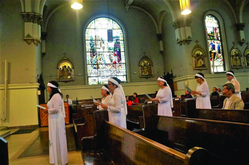 Women from Our Lady of Lavang Vietnamese Catholic Community take part in the Good Friday 15-station lamentation to mourn the suffering and death of our Lord. The white headband and outfit are customary to wear at the funerals of loved ones.  (Courtesy Photo)