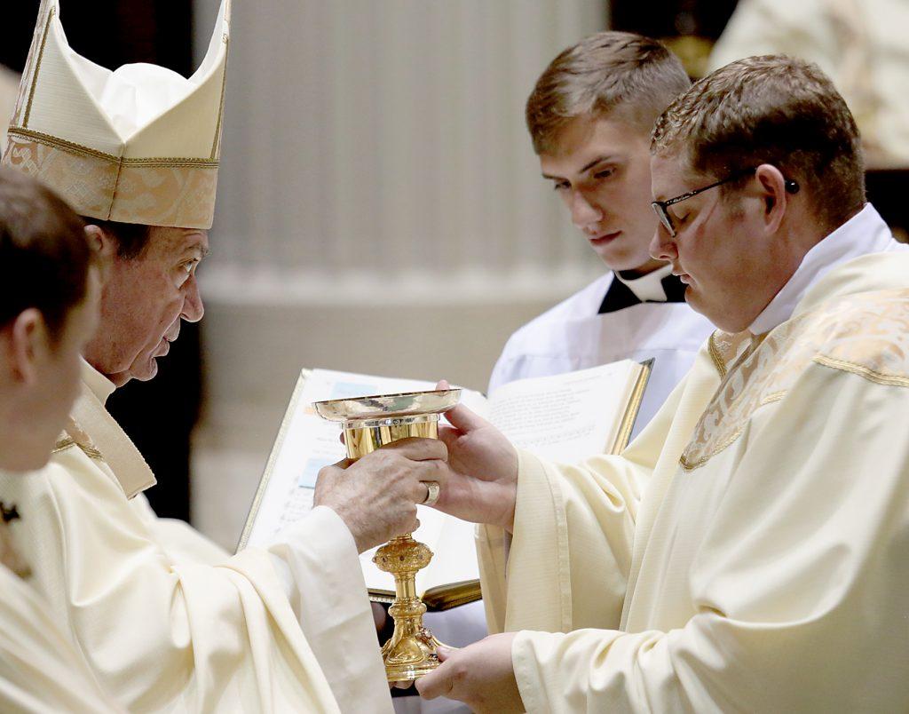 Father Zach Cecil receives the chalice and paten (CT Photo/E L Hubbard)
