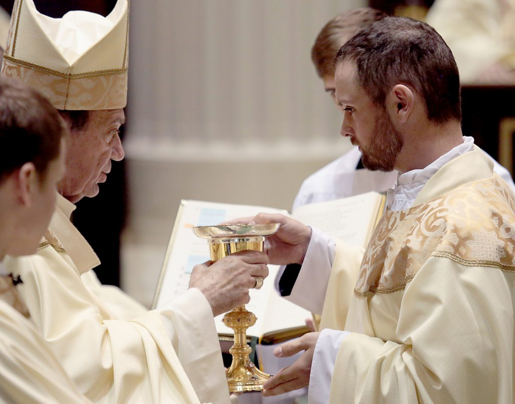 Father Jedidiah Tritle receives the chalice and paten. (CT Photo/E L Hubbard)