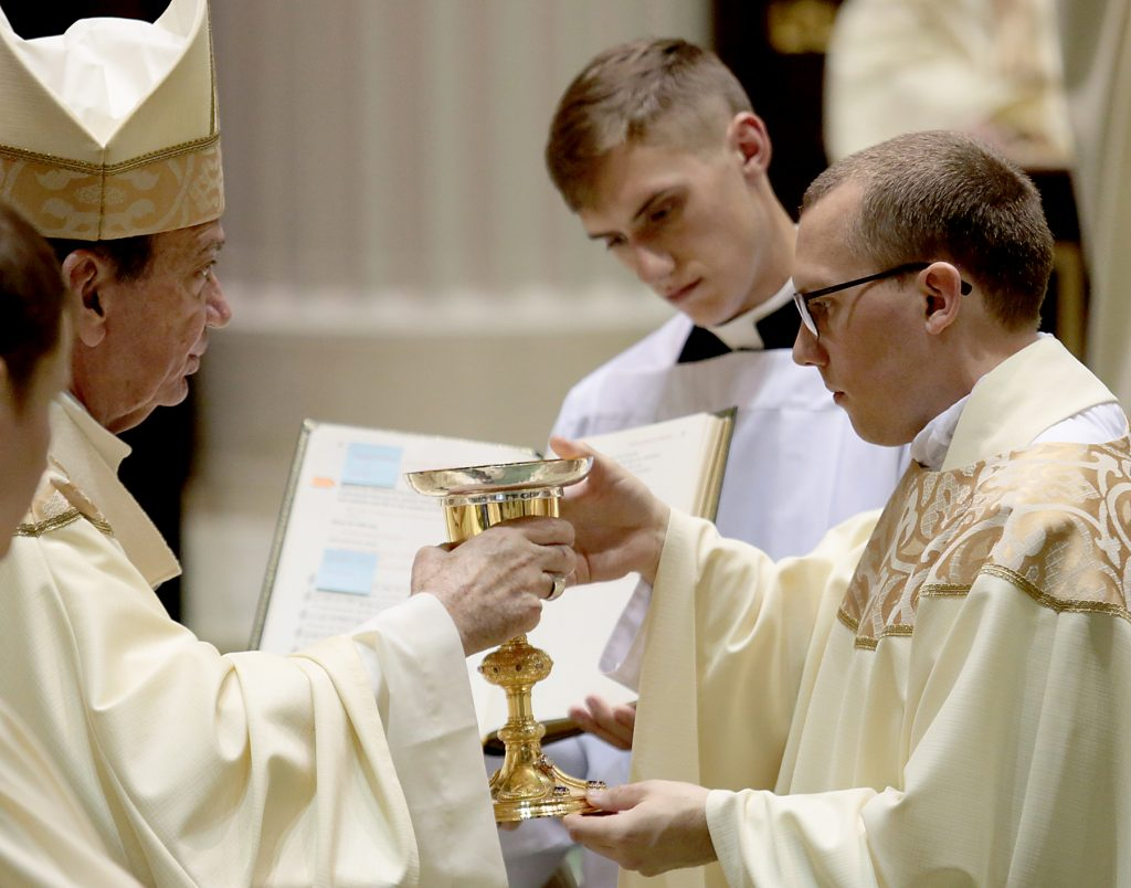 Father Jeffrey Stegbauer receives the chalice and paten. (CT Photo/E L Hubbard)