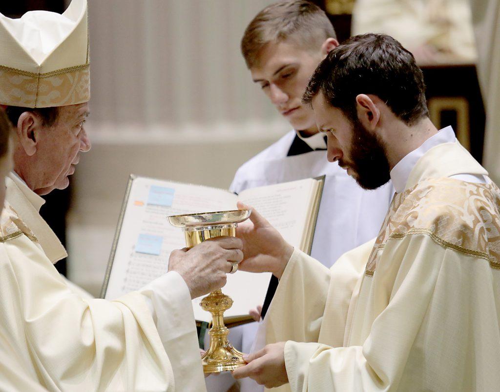 Father Ambrose Dobrozsi receives the chalice and paten. (CT Photo/E L Hubbard)