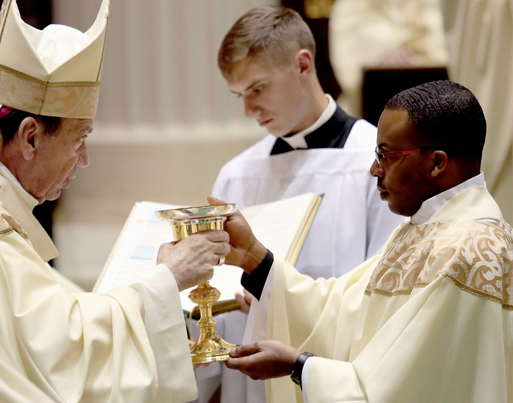 Father Alex Biryomumeisho receives the chalice and paten (CT Photo/E L Hubbard)