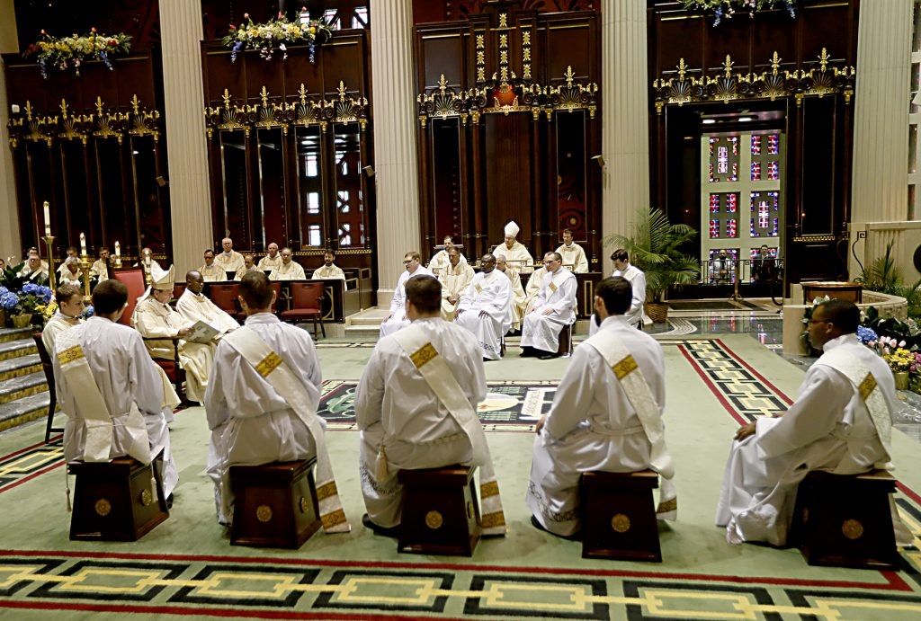 The ordinands listen to the homily from Archbishop Dennis Schnurr. (CT Photo/E L Hubbard)