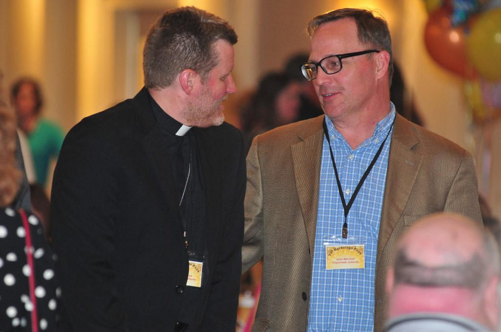 Fr.Bob Jones, Chaminade Julienne HS and John Marshall also from CJHS socialize prior to supper being delivered (CT Photo/Jeff Unroe)