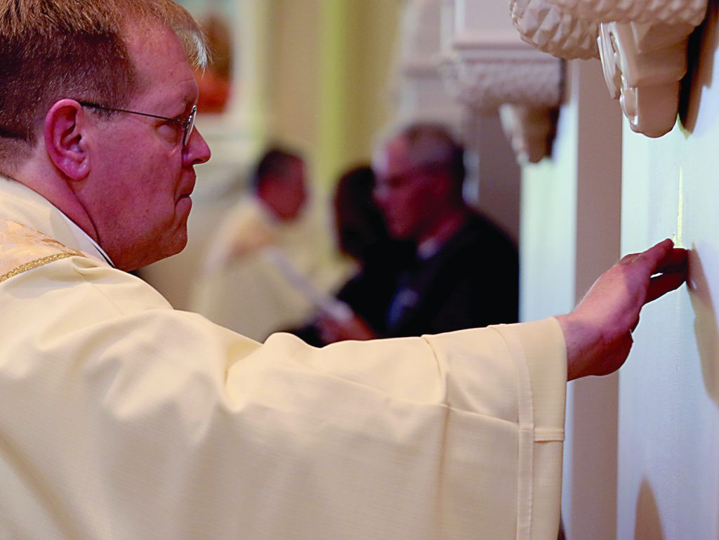 Father Jeffrey Kemper annoints the walls during the dedication of St. John the Baptist Church in Harrison Saturday, June 1, 2019. (CT Photo/E.L. Hubbard)