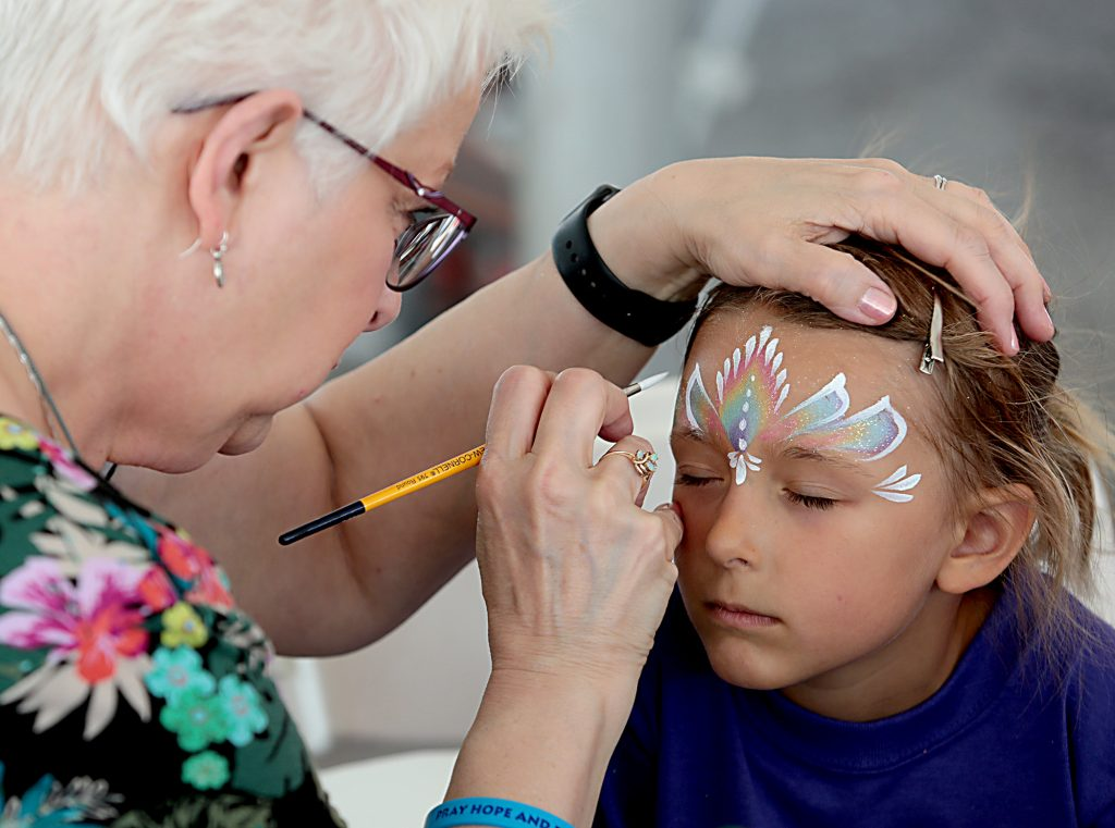 Theresa Morris paints the face of Marie Hicks, 5, during the Cross the Bridge for Life in Newport, Ky. Sunday, June 2, 2019. (CT Photo/E.L. Hubbard)