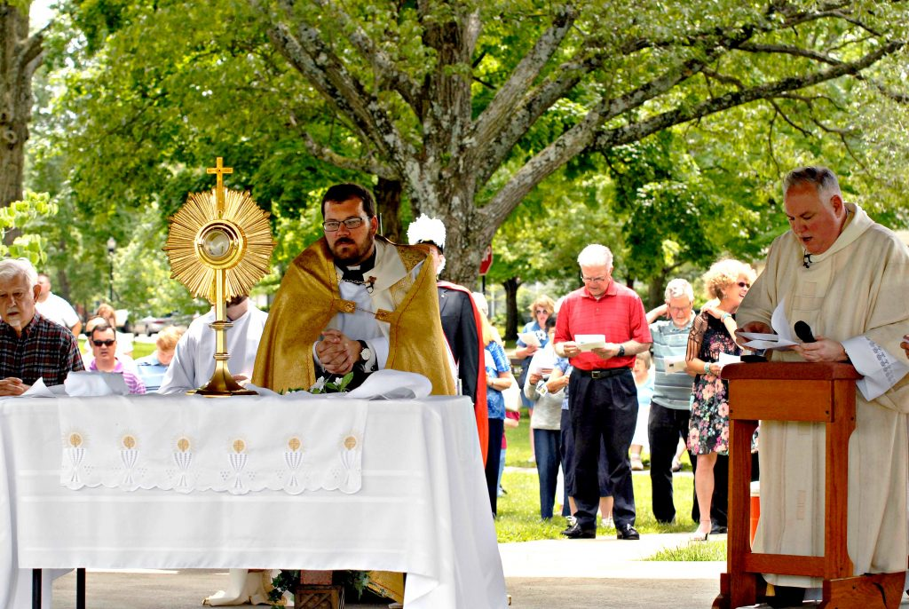 Father Alex McCullough, pastor of Our Lady of the Rosary in Greenhills, kneels before the Blessed Sacrament as the congregation sings a hymn during the church's Fourth Annual Feast of Corpus Christi Procession on Sunday, June 23. (CT Photo/David A. Moodie)