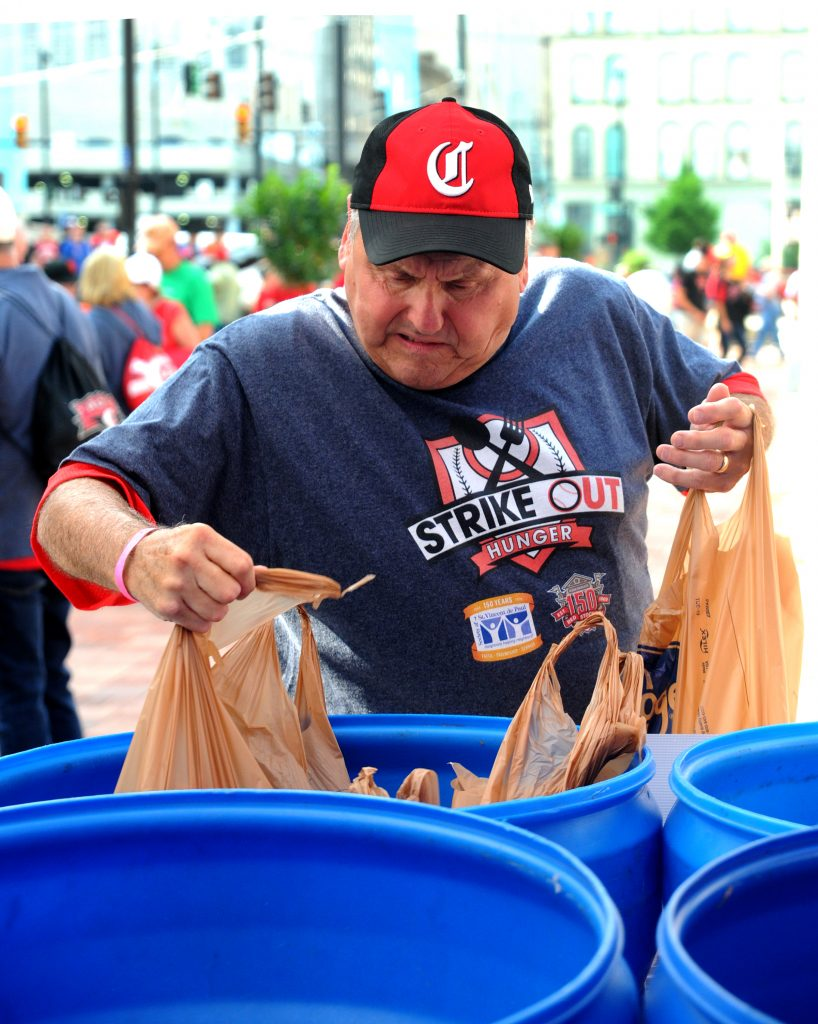 """St. Vincent de Paul volunteer Steve Taylor places bags  of donated food into a collection bin outside of Great American Ballpark on Friday, May 31. SVdP collected food from patrons of the Reds games on Friday and Saturday, May 31 and June 1, during  their """"Strike Out Hunger"""" campaign. Game patrons who donated three or more non-perishable foods were awarded tickets to  a future Reds game. Last year's drive collected over three tons of food, which fed approximately 5,300 families. (CT photo/David A. Moodie)"""