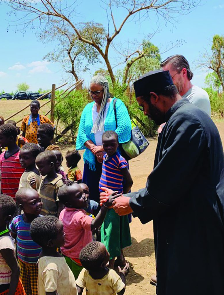 Abba Habtesilassie Antuan, General Secretary of Eparchy of Emdibir Catholic Secretariat, is pictured with Rita Winters and the group of Cincinnati visitors, as he checks in with a low-income area of his parish where sharecroppers are struggling to earn enough money to stay alive.