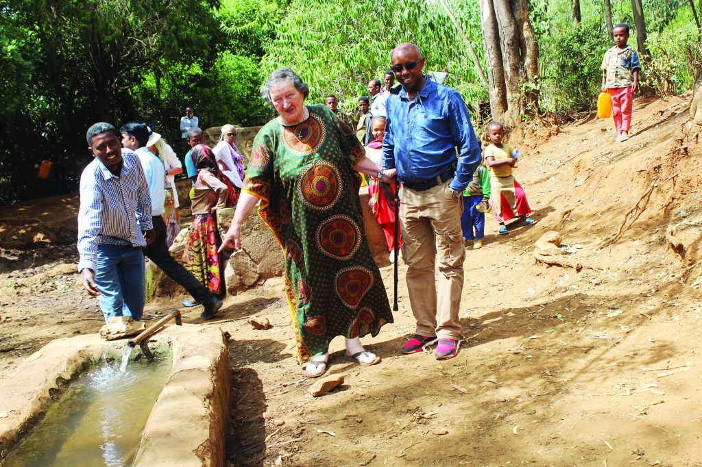 Medical Mission Sister Elaine Kohls and local residents visit a well in rural Ethiopia.