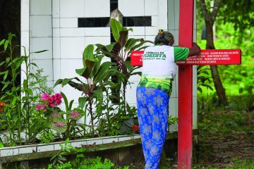 Antonia Silva Lima, a farmer in the Brazilian Amazon, prays at the grave of U.S.-born Sister Dorothy Stang in Anapu, Brazil. Sister Stang was assassinated in 2005. The red cross beside her grave bears the names of 16 local rights activists who have been murdered since her killing. Church activists say the killings continue, and they're about to erect a second red cross with even more names. (CNS Photo/Paul Jeffrey)