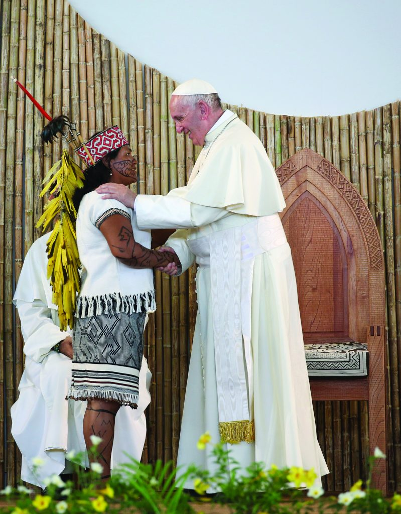 """Pope Francis is greeted by a member of an indigenous group from the Amazon region during a meeting at the Coliseo Regional Madre de Dios in Puerto Maldonado, Peru, Jan.19, 2018. The upcoming Synod of Bishops on the Amazon is an """"urgent"""" gathering, not of scientists and politicians, but for the church whose main focus in discussions will be evangelization, Pope Francis said in a new interview. (CNS photo/Alessandro Bianchi, Reuters)"""