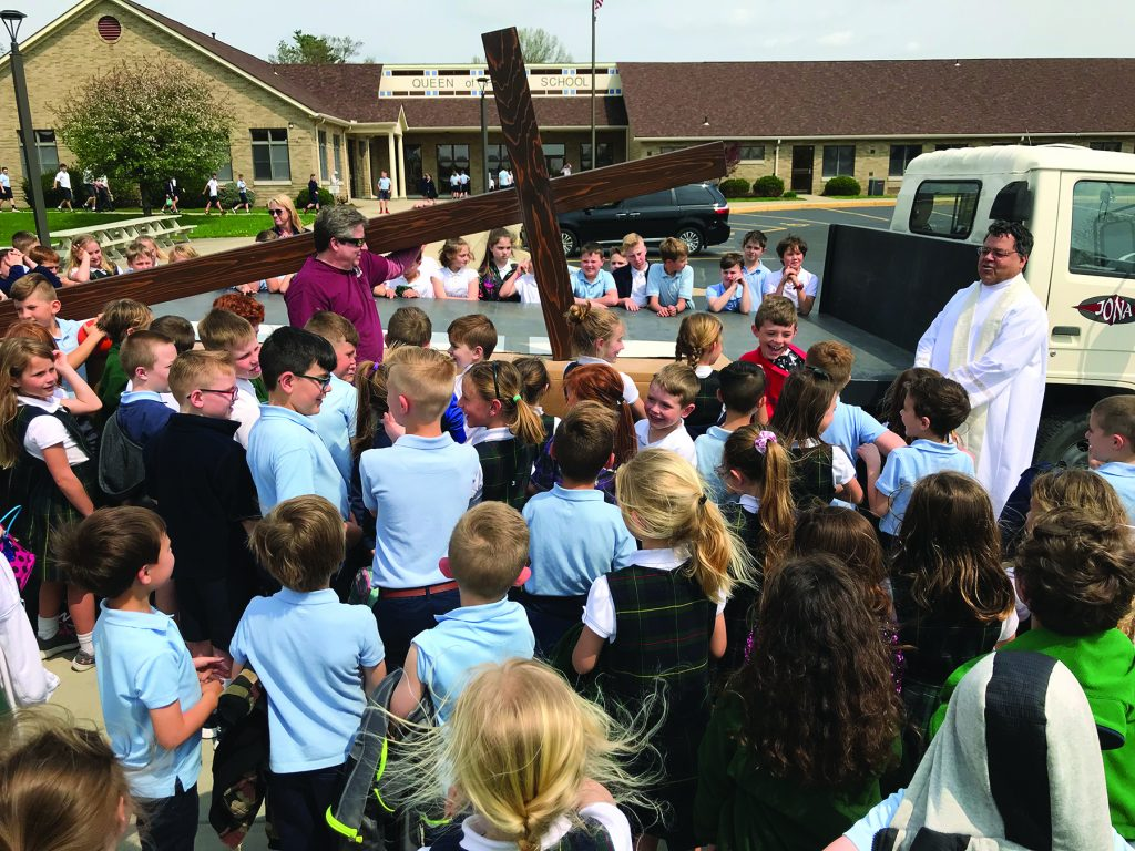 Queen of Peace Parish in Hamilton replaced their outside cross atop the church that was originally built and erected in 1966. The new cross is larger and lit for the entire Queen Acres neighborhood. They placed the old cross inside the new one. Students witnessed the blessing of the new cross.