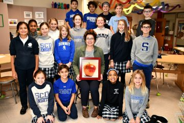 Samantha England with sixth graders at Summit Country Day School. She holds her painting of an apple, part of her personal perseverance project