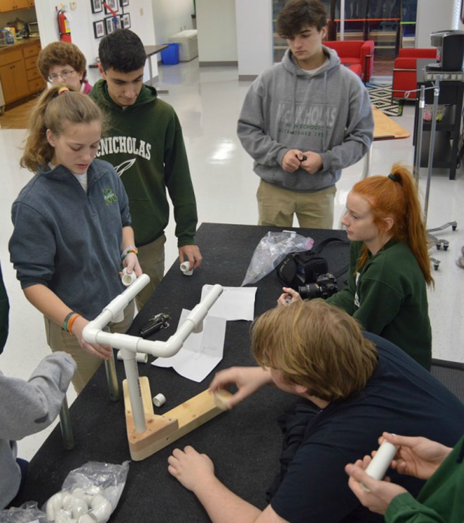 McNicholas High School's engineering classes have been partnering with alumnus Bill Deimling and his non-profi, May We Help, which designs, creates and builds specialty devices for people with disabilities at no charge. McNicholas engineering students designed a prototype of a machine that students with limited mobility at the Margaret B. Rost School could use to help fill bags.