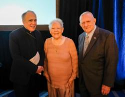 Cardinal Daniel N. DiNardo of Galveston-Houston poses with Gene Kranz, right, former flight director for Apollo 11, and his wife, Marta, during the 2019 Archdiocese of Galveston-Houston Prayer Breakfast in Houston July 30. Gene Kranz, who served as the event's speaker, is a parishioner at Shrine of the True Cross Catholic Church in Dickinson, Texas, near Houston. (CNS photo/James Ramos, Texas Catholic Herald)