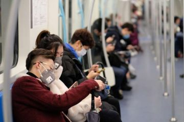 People wearing surgical mask sitting in subway in Shanghai, China. Credit: Robert Wei/Shutterstock