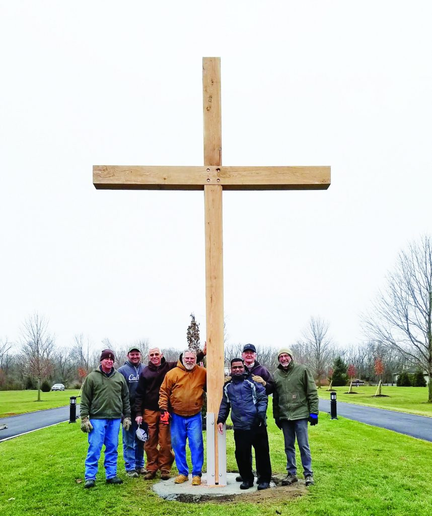 Joe Fisher, Ben Dull, Bill Platfoot, John Marchal, Father Michael Samala, Dennis Hile, and Bob Iiames with the cross built from tornado debris