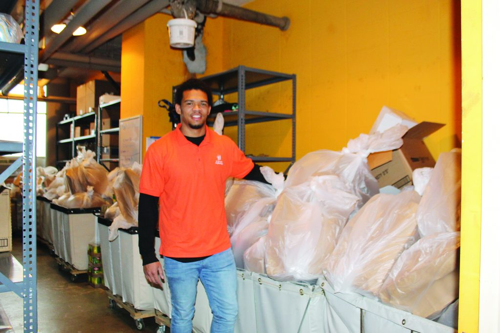St. Joseph Orphanage's Behavior Support Specialist, Willie Wright, packs bags of food alongside other education team members to be delivered to the homes of students.