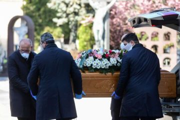 Undertakers wearing face masks carry a coffin in a cemetery in Bergamo, Italy, March 16, 2020. Credit: AFP via Getty Images